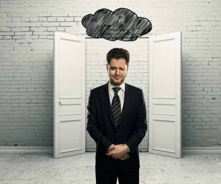 above head: Sad businessman with abstract dark cloud sketch above head in white brick interior