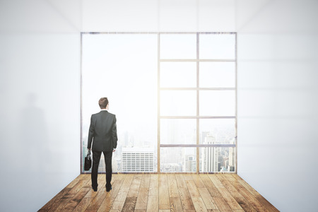 looking at view: Businessman looking out of large window in interior with concrete walls, wooden floor and city view. Research concept. 3D Rendering Stock Photo