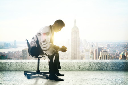 Young businessman with anger issues sitting on rooftop with New York city view and sunlight. Double exposure