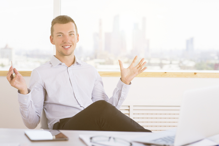 handsign: Portrait of cheerful young businessman showing size of something in bright office interior Stock Photo