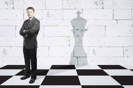 Businessman with folded arms standing on chessboard with king piece shadow on textured brick tile wall. Leadership concept