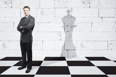 Hombre de negocios con los brazos cruzados de pie en el tablero de ajedrez con el rey pieza sombra en la pared de ladrillo con textura de baldosas. concepto de la dirección Foto de archivo