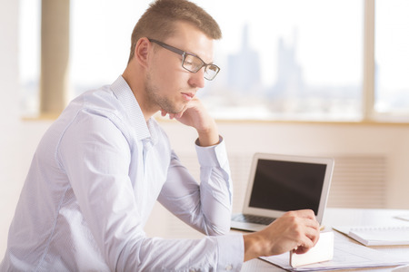 Side view of focused young businessman doing paperwork at wooden desk with blank notebook screen in modern bright office interior