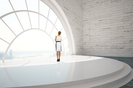 view window: Businesswoman standing in brick interior design with stairs, round window, city view and daylight. 3D Rendering