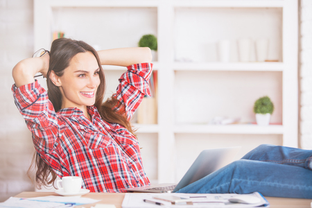 behind: Beautiful young woman with pretty long hair relaxing in office with hands behind head
