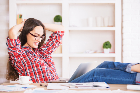 hands behind head: Attractive young lady with beautiful long hair relaxing in office with hands behind head Stock Photo
