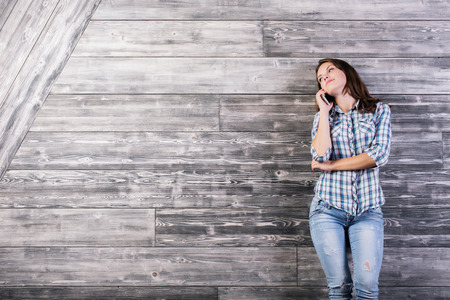 casual woman: Attractive european woman in casual shirt talking on mobile phone. Textured wooden wall with copy space in the background Stock Photo