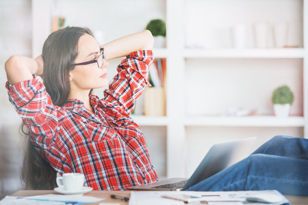 break from work: Gorgeous young female with beautiful long hair relaxing in office with hands behind head Stock Photo