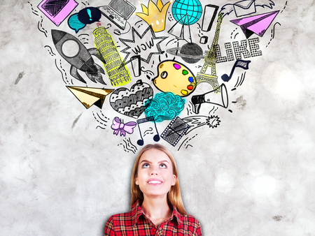 Portrait of young woman looking up on concrete background with travel, startup, social media and communication sketches