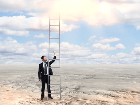 Businessman in suit holding tall ladder on desert background. Success concept