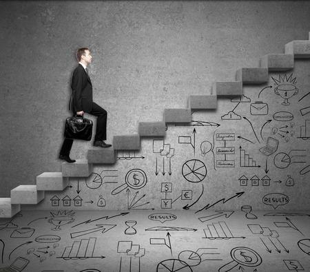 Hombre de negocios con maletín escalada abstracta escalera de hormigón con dibujos comerciales por debajo
