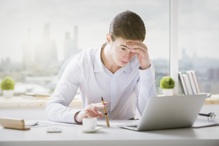 Portrait of handsome caucasian guy with pen in hand using laptop computer at office desk with coffee cup, paperwork and other items. Blurry city background