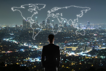 Travel concept with businessman looking at anstract map on illuminated night city background Stock Photo