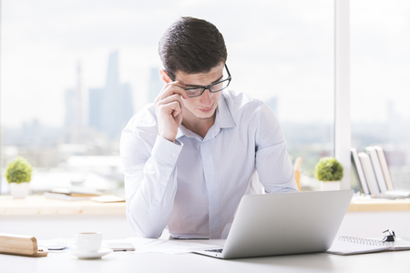 Portrait of handsome guy in glasses using laptop computer at office desk with coffee cup, paperwork and other items