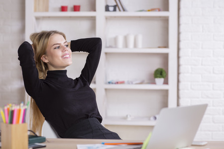 hands behind head: Portrait of smiling young woman with hands behind head relaxing and daydreaming at workplace Stock Photo
