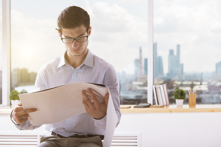 amendment: Attractive young architect with pencil behind ear going through construction project at workplace with blurry city view and sunlight Stock Photo