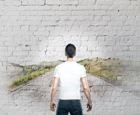 countryside road: Back view of casual young man looking at abstract countryside road drawing Stock Photo