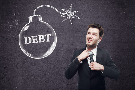 choking: Debt concept with choking businessman and bomb sketch on concrete wall background Stock Photo