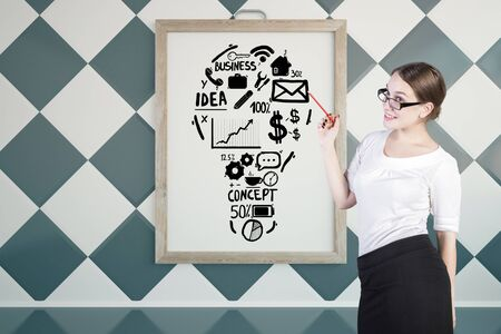 idea sketch: Young businesswoman giving presentation on business with lightbulb sketch in picture frame. Chessboard wall background. Idea concept