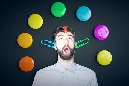 Funny image of surprised young man with pin on forehead, clips on ears and colorful button magnets around on dark background