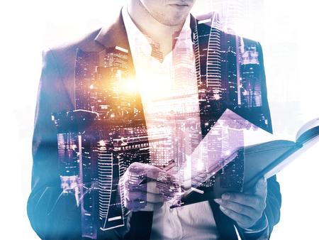 Geschäftsmann Buch auf abstrakte Stadt Hintergrund mit Sonnenlicht zu lesen. Doppelbelichtung