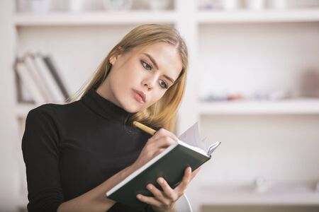Attractive european woman taking notes in diary at modern bright workplace with items on shelves