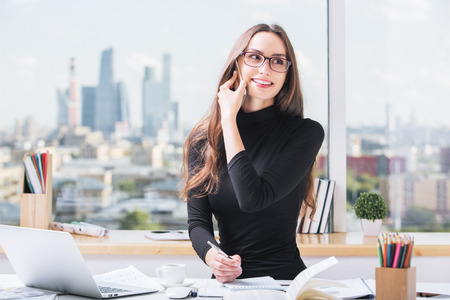 Portrait of cheerful european businesswoman at office desk talking on cellular phone, working on project and doing paperwork. Blurry city view in the background