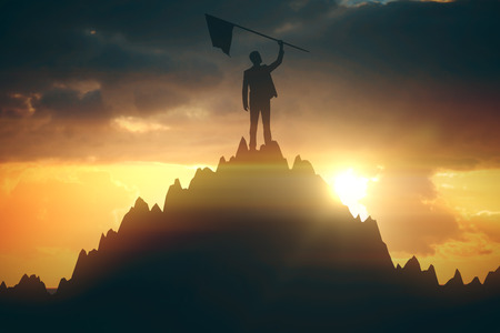 Silhouette of businessperson with winner's flag on mountain top. Abstract background with sunlight. Leadership concept. 3D Rendering
