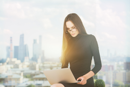 city view: Portrait of beautiful european businesswoman using laptop while sitting against window with blurry city view and sunlight