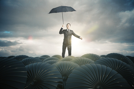 stormy sky: Businessman with black umbrellas on stormy sky background. Business protection concept. 3D Rendering