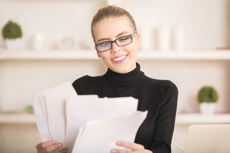 revisando documentos: Portrait of attractive smiling woman dealing with paperwork in modern bright office with various items on shelves