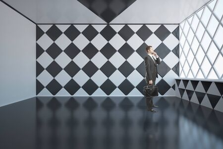 daylight: Pensive businessman with briefcase standing in empty abstract interior with chessboard patterned walls and windows with daylight. 3D Rendering Stock Photo