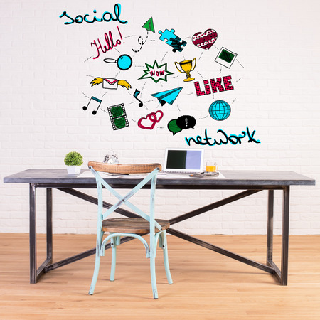 creative communication: Modern workplace with creative communication icons sketch on white brick wall. Social media concept Stock Photo