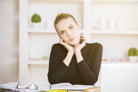 Portrait of pretty young female sitting at table in modern office with various items on white bookshelf