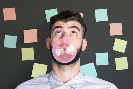 bubblegum: Portrait of surprised caucasian man blowing bubble with pink gum on dark background with colorful stickers Stock Photo