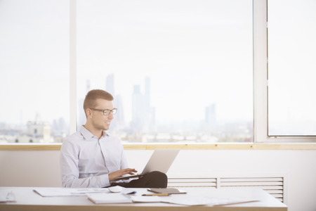 businessman in office: Smiling young businessman using laptop computer in modern brigth office interior with city view and daylight