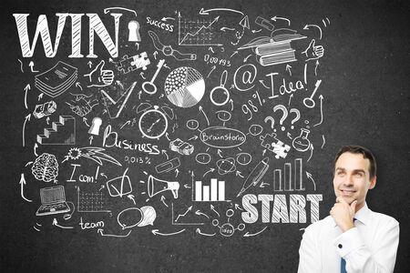 Riflessivo giovane imprenditore in piedi contro il muro di cemento con creativa abbozzo di business. Leadreship e il concetto di successo