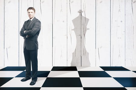 chess player: Businessman with folded arms standing on chessboard with king piece shadow on textured wooden wall. Stock Photo