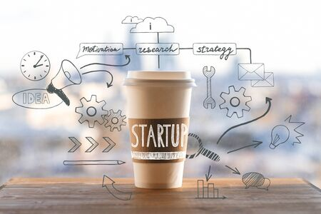 take away: Startup concept with take away coffee cup and abstract business drawings on wooden desktop and blurry city view background