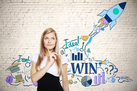 Attractive thoughtful businesswoman standing against brick wall with creative space ship sketch. Startup concept