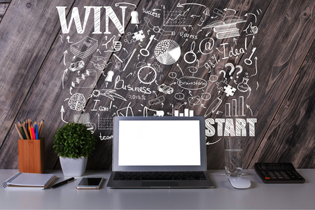stationery items: Front view of creative designer workplace with blank laptop screen, plant, stationery items and business sketch on wooden wall background. Mock up.