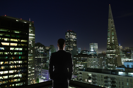Businessman on rooftop looking at illuminated night city.