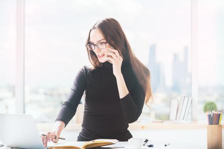 hablando por telefono: Retrato de muchacha europea hermosa en el escritorio de oficina hablando por teléfono móvil y utilizando equipo portátil. vista borrosa ciudad en el fondo