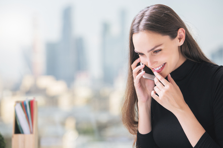 Portrait of happy smiling businesslady having cell phone conversation on blurry city background Stock Photo