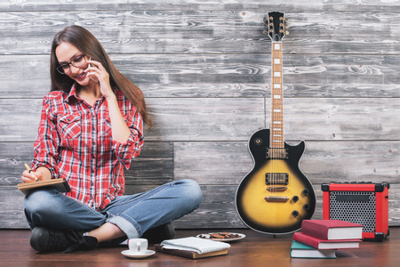 guitar amplifier: Pretty young woman sitting on wooden floor with electric guitar, amplifier, books, food, coffee cup, other items, talking on phone and writing in notepad Stock Photo