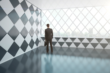 Young businessman with briefcase standing in empty abstract interior with chessboard patterned walls and windows with city view. 3D Rendering