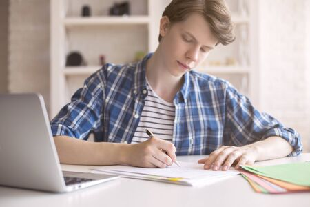 working on school project: Close up of casual young man working on coursework at desk with blurry laptop. White brick wall and shelves in the background Stock Photo