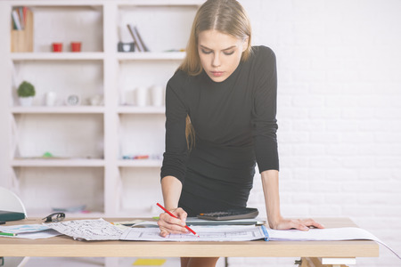 Attractive female designer leaning on desktop and drawing interior project. Shelves with various items in the background