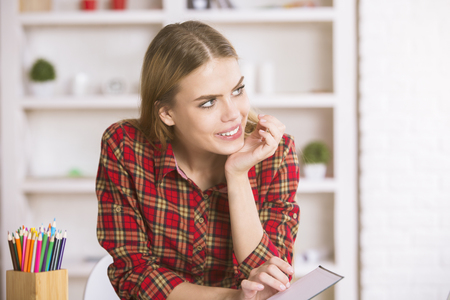 Portrait of thoughtful smiling girl sitting at table in modern office with various items on white bookshelf
