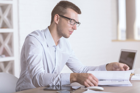 deal making: Side view of concentrated young businessman doing paperwork at wooden desk with blank laptop screen in modern bright office interior